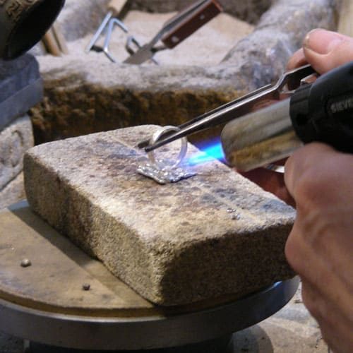 silversmithing a silver ring with a torch